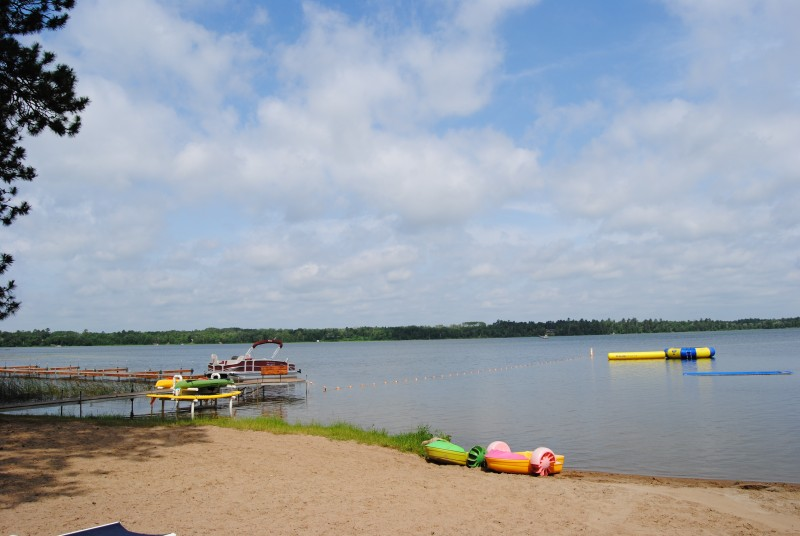 Lake dock with kayaks, and beach with inflatables.