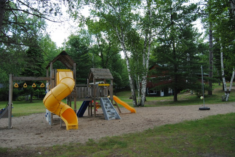Wooden playground with slides, tetherball and sandy ground.
